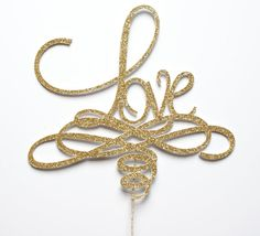 """Gold glitter """"Love"""" cake topper.  This is a double-sided topper die cut on heavy glitter stock.  Perfect for weddings, bridal shower and celebrations.  (Includes stake for inserting into your cake)  Also available in Gold, Bronze, Hot Pink, Aqua, Green, Black and White glitter stock.  Plea..."""