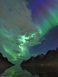 This magnificent shot of the Northern Lights shows the them reflecting off the clouds and lake in Norwaywww.dailymail.co.uk