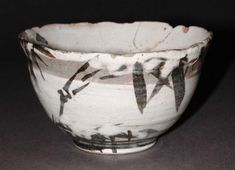 Stoneware footed food bowl with foliate rim, thrown and turned. Red buff body covered with white slip leaving the body showing in a band below the rim. Decorated with bamboo in black and then further patches of white slip (to indicate snow), and final cover of clear glaze. Japanese, by Ogata Kenzan