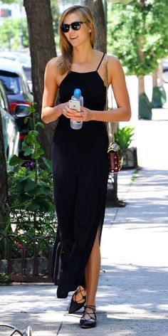 PULL OFF AN UNSEASONAL COLOR Summer is typically all about white, brights, and pastels. Take the alternative route and pull off top-to-toe black, like Karlie, in a strappy breezy jumpsuit, a chain-strap purse, and black lace-up Michael Kors flats.