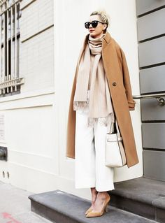 Blair Eadie wears a neutral top, scarf, camel coat, white culottes, suede pumps, oversized black sunglasses, and a white leather tote