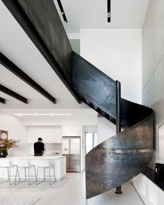 This sleek raw-metal staircase imitates the color of the exposed steel beams and recessed track lighting up above