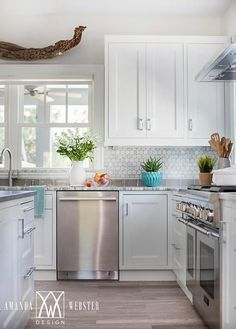 Well appointed cottage kitchen is fitted with stainless steel appliances including a stainless steel oven range positioned under a stainless steel hood and a stainless steel dishwasher positioned beneath a gray quartzite countertop accenting white cabinets.