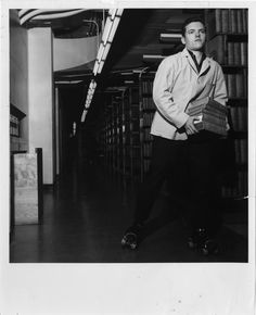 "young man, holding several books, roller skating through the stacks at the Detroit Public Library. Label on back: ""Roller skates used to expedite book service, level A, Cass Ave., Wings."""