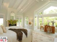 love this…the ceilings, fireplace and windows with views of trees and doors leading outside…perfection