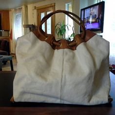Beautiful Authentic Michael Kors handbag Authentic Michael Kors handbag. Beautiful white leather with brown trim. It has gold/ brass spikes on the bottom. It has magnetic snaps for closure. It is teally a clean bag with no major flaws, holes, or pen marks. It is also very large MICHAEL Michael Kors Bags Satchels