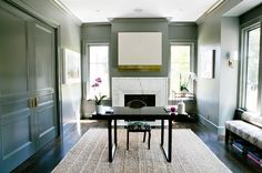 Home office features walls and moldings painted gray lined with a modern marble fireplace under white and gold art flanked by windows with a bar cart placed under one window.