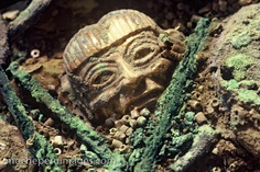 Photograph of a gold head ornament buried in the Moche (Mochica) royal tomb treasure of the Old Lord of Sipan in the Lambayeque Valley of Northern Peru. The metalwork sculpture head is a 2-inch bead from a set of ten beads that made a necklace for the warrior priest Old Lord of Sipan. The bead is resting on gilded copper jewelry (now corroded green) and beads.