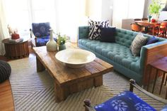 Love the rustic coffee table.  I am not wild about the retro design of the couch, but love the use of color.