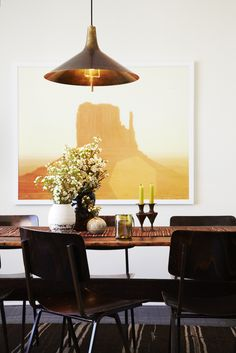 Industrial brass lamp above dining table with flowers and orange art