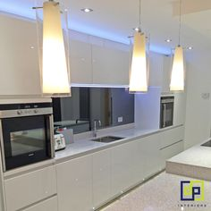 Contemporary white gloss kitchen with smoked mirror glass & blue uplights