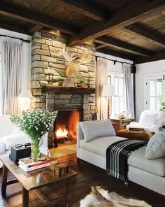 Warm Country Living Room    Two furniture groupings in one room create a layered and cosy effect.      In this Muskoka cottage designed by Michael Angus, ceiling-mounted spotlights cast a warm glow onto this natural stone fireplace. A low-slung daybed serves as a room divider while keeping sight lines open.