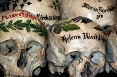 """The Halstatt Painted Skulls Ossuary was built back in the 12th century when the village was flourishing, the population exceeded 3000 souls and there was no more room in the cemetery, so the authorities had to come up with some kind of solution. They decided to """"rent"""" graves, if you will, bodies would be buried for only 10-15 years before being dug up, and the skulls removed, in order to make room for other corpses. The skull would then be cleaned, aired & decorated."""