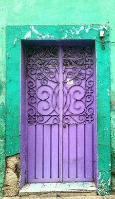 Purple door & Turquoise facade adds a lot of pop to this scrolled door… Knobs And Knockers, Door Knobs, Door Handles, Beautiful Front Doors, Unique Doors, Door Entryway, Entry Doors, Purple Door, When One Door Closes