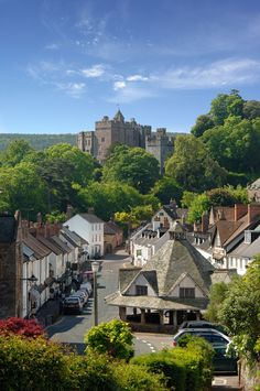 Dunster village in Somerset, England, in the distance the Norman Dunster Castle. Dunster was the birthplace of the song 'All Things Bright and Beautiful' when Cecil Alexander was staying with Mary Martin, the daughter of one of the owners of Martins Bank