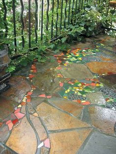 Backyard Landscaping Ideas - A whimsical grapevine, with colorful tile leaves and cullet glass clusters of grapes, on a stone porch built by Jim DuBois