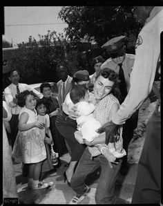 Title:  Sheriff Deputies carry Aurora Vargas from Chavez Ravine home  Eviction Scuffle--Deputies have a hectic time evicting family from house in Chavez Ravine today. Above left, resisting Aurora Vargas is carried down stairs from porch  Creator/Contributor:  Anonymous, Photographer  Los Angeles Times (Firm), Publisher  Date:  May 9, 1959  Contributing Institution:  UCLA, Special Collections, Young (Charles E.) Research Library