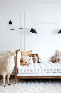 Nursery with a daybed, stuff animals, and a black wall sconce