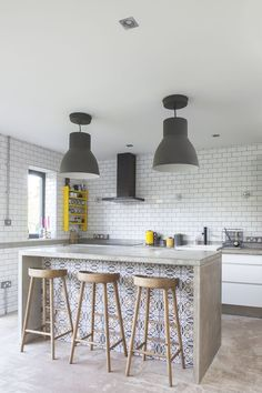 We love the large industrial lights and weathered oak bar stools in this kitchen
