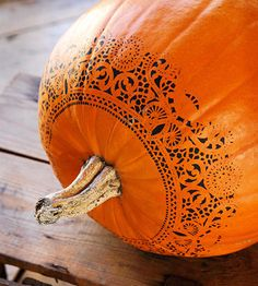 Get this lacy pumpkin look by using a doily as a stencil.| Happy Halloween | Pumpkin Carving | Pumpkin Painting | Fall Decor | Find Instructions for stenciling at www.bhg.com