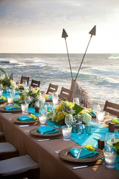 A modern beach table setting - With neutral brown tones, zingy aqua blue runners & napkins & lime & yellow flowers to highlight