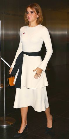 Emma Watson arrived at the HeForShe 2nd Anniversary reception in a very minimalist look, featuring a tiered white dress with a black sash tied around her waist, an adorable ring-handle Simon Miller purse, and suede pumps.