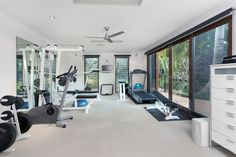 Home gym with exercise bike, weights, treadmill and weight machines in white color scheme