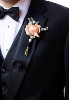Boutonniere - a single peach ranunculus, silver brunia, and black and gray ribbons