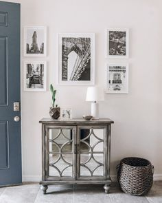 Entryway styled with a grey mirrored credenza (mirrored cabinet, grey cabinet, grey credenza), a grey whicker basket for storage, a mini white table lamp, a small mercury glass planter and black and white prints.  Neutral entryway, chic entryway, transitional entryway, entryway decorations, entryway ideas.