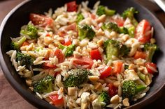Italian dressing, feta and almonds give this orzo salad great flavor, but the festive color comes from broccoli and cherry tomatoes. Now it