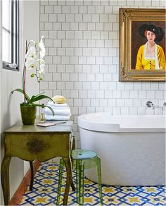 A maze of blue and yellow patterned tiles make the painting above the bathtub pop in this quirky, eclectic bathroom.