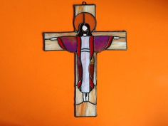 This is a vintage old stained glass crucifix. This beautiful piece shows jesus on the cross. It has copper beaded edging with an aged patina and a hook eye on top for wall hanging. Some of the stain glass is Iridescent and the crucifix looks really cool with sunlight beaming through it. It is a good size measuring 17 1/2 inches by 13 inches.