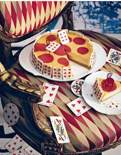 This is a really wierd picture! Pizza. Cake. Pizza Cake. Cards. Cards on a cake. Cake on a chair. A chair on a piece of cake that is on a chair!...WHAT IN THE WORLD?!