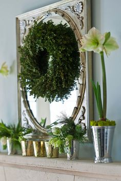 A silvered mirror above the cast stone honed limestone fireplace is part of the pretty mix of silver, gold and white. A boxwood wreath tops the mirror, and a mix of votive candles and julep cups filled with tulips and amaryllis keep things young and light.