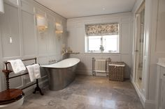 Panelled bathroom, hand painted in Farrow & Ball - Pavilion Grey. Wall lights by Porta Romana and down lighters by John Cullen. The luxurious bath is an Ashton & Bentley - Aegean, taps by Lefroy Brooks #portaromana #panelledbathroom #wallpanelling #farrowandball #interiordesign #ashtonandbentley #aegean #lefroybrooks