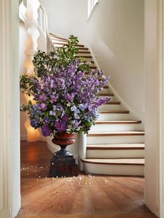 So beautiful! Hardwood floors frame this opulent staircase. The giant lilac floral arrangement somehow totally works!