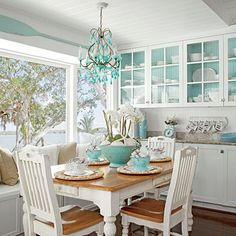 Pops of turquoise in this breakfast nook make the white decor pop; see how the white dinnerware contrasts against the painted shelves?
