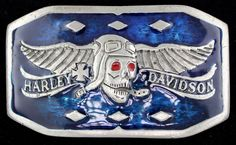 """Highly collectible and very hard to find! Winged aviator skull belt buckle featuring the words """"Harley Davidson"""" an iron cross and beautiful blue enamel inlay on the background with red enamel inlay on the skulls eyes. 