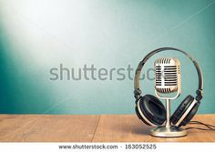 Microphone and headphones on table in front aquamarine wall background by BrAt82, via Shutterstock