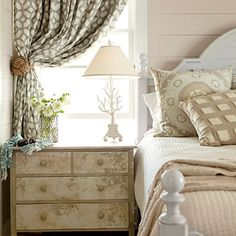 Neutral Bedroom: Create Interest With Pattern and Finishes:: The bedside location in this guest room was the ideal spot for a vintage chest that Chapman had faux-painted and sealed with a crackle glaze. A graphic print on the custom curtains brings modern flair to the neutral palette and linens. Photographer: John Ellis, Stylist: Elizabeth Beeler.. Coastal Living