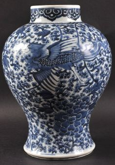 AN EARLY 18TH CENTURY CHINESE BLUE AND WHITE BALUSTER JAR Late Kangxi, painted with a phoenix bird amongst boldly floral sprays. 13. 5ins high.