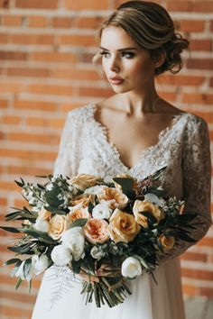 Gorgeous bride in lace gown with flowing skirt from Pearl & Dot Bridal Boutique; holding a bouquet of white tulips, white ranunculus, Juliet garden roses and Camel roses with olive branch and eucalyptus foliage. Photo: @gwilkingsphoto Florals: www.flowersbyjanie.com HMUA: http://www.somethingborrowedbeauty.com/