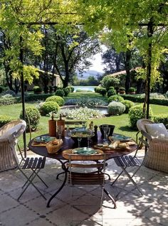 lovely patio paving, French bistro  & wicker furniture, vine-covered pergola, & a relaxing vista