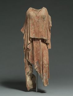 This terracotta model depicts a female figure wearing a peplos, a popular garment for women in ancient Greece from the fifth century B.C. onward. It is usually made of a single piece of wool folded over at the top and fastened at the shoulders, leaving open the left side of the garment.  5th century Greek. 06.1151 MET