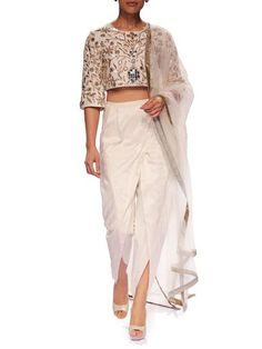 This indian suit is the perfect embodiment of Payal Singhal's unrivalled take on modern yet classic femininity. Payal juxtaposes menswear-inspired dhoti pants with the biggest trend in the last three years, the cropped top. The top is rendered in beautiful ivory dupion silk with hand embellished zardosi and leather applique. The outfit takes on a whimsical feminine finish with a tulle dupatta (stole). 100% dupion silk Dry clean