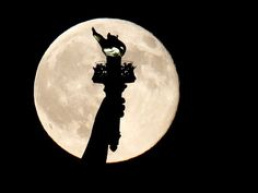A blue moon rises behind the torch of the Statue of Liberty,  seen from Liberty State Park in Jersey City, N.J., on July 31, 2015. A blue moon happens when the moon rises in its full stage twice during the same month.  Julio Cortez, AP