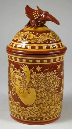 "Cape Cod Girl lidded storage jar – R.Geering    A lidded storage jar with a bird finial. The mermaid, whale, moon and fish pattern in sgraffito into a traditional red clay body is a contemporary design inspired by the old whaling song ""Cape Cod Girls""."