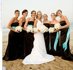 Floor-length gowns lent a formal air to the seaside wedding, while the turquoise sashes picked up the color of the ocean.