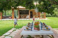 O espaço mais encantador do sítio Marigold é o pátio gourmet, onde as pessoas passam o dia todo curtindo as delícias da vida ao ar livre. O espaço é simples: sobre um piso de cacos de pedra mineira, está a mesa que acomoda 12 pessoas, com tampo de concreto armado e revestimento de cimento queimado. O projeto é do arquiteto André Luque