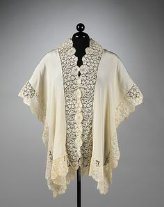 The cut of this dressing jacket is very minimal, similar to some traditional folk garments. Additionally, the shape of the jacket shows the interest in such forms that Paul Poiret and Madeline Vionnet were presenting during that time. It is a very beautiful example of machine-made lace, which is clearly an imitation of the flat Flemish handmade laces.